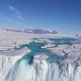 A 400-foot-wide waterfall drains off the Nansen Ice Shelf into the ocean. (Image by Won Sang Lee/Korea Polar Research Institute)