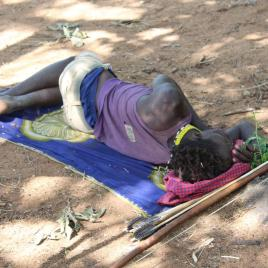 A Hadza man sleeps on the ground on an impala skin in northern Tanzania. (Image by David Samson)